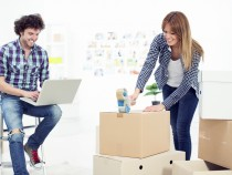 Cheerful young couple moving to new apartment
