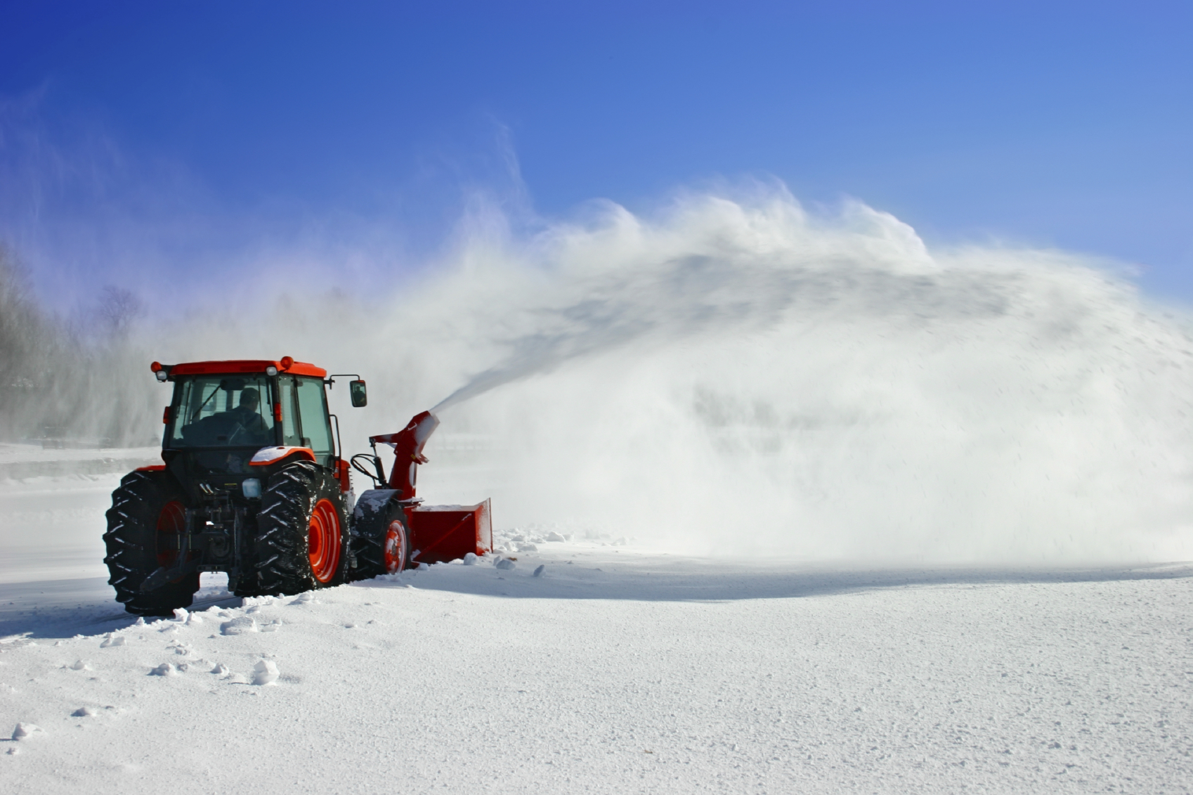 Snow is being removed by a snow blower.