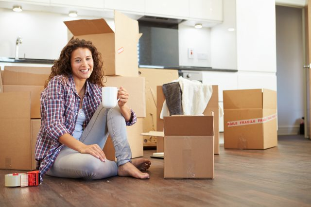 Woman with coffee cup surrounded by moving boxes