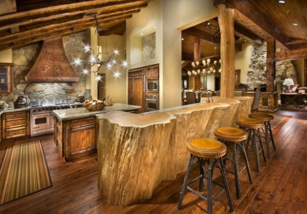 rustic-cabin-kitchen-design-with-log-wood-bar-table-and-unique-chandelier-on-vaulted-ceiling-over-marble-countertop-kitchen-island-also-natural-stone-backsplash-plus-copper-range-hood-615x429