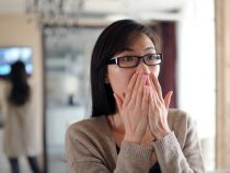 Asian woman is watching news on TV with shocked expression2011-3-11 Japan 9.0 Earthquake & Tsunami