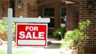 "Red and white ""Home for Sale"" sign in front of a red brick house that is for sale. Green grass and bushes indicate the spring or summer season. Front porch and windows in background. Real estate sign in residential neighborhood.  Moving house, relocation concepts."