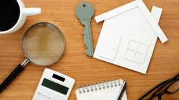 House and key shaped paper cutout, calculator and magnifier on wooden table.