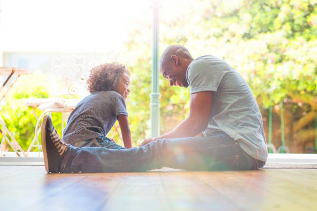 A photo of happy father and daughter sitting on floor. Smiling girl looking at man. They are sitting at the entrance of house.