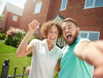 a young couple celebrate getting the keys to their new home by taking a selfie in the garden .