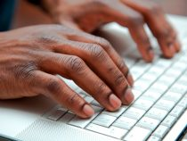Close up of African hands on a keyboard