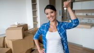 Happy young woman holding keys to her new house while packing and looking at the camera smiling - moving house concepts