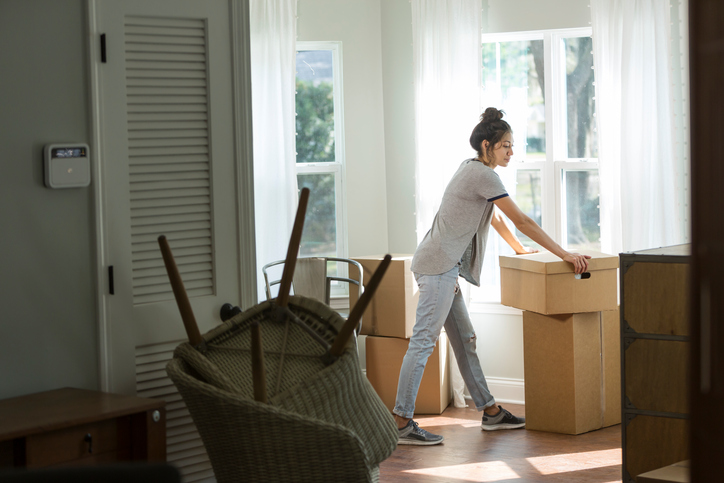 A young mixed race woman, Hispanic and Pacific Islander ethnicity, moving into a house or apartment. She is lifting a cardboard box indoors by a sunny window.