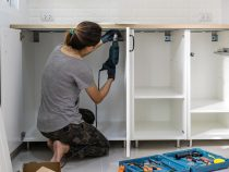 Young woman using electric screwdriver to installation kitchen furniture, DIY concept