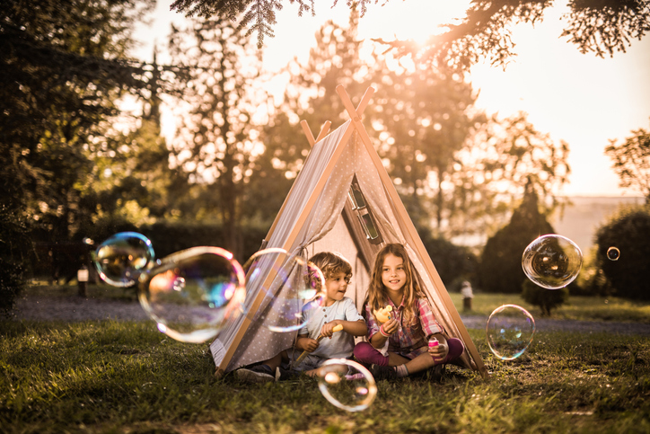 Small kids playing with bubble wand in front of a tent outdoors.