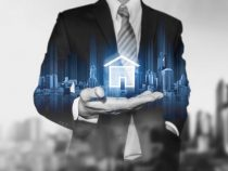 Businessman holding modern buildings hologram, and home icon. Real estate business, building technology and smart home concept