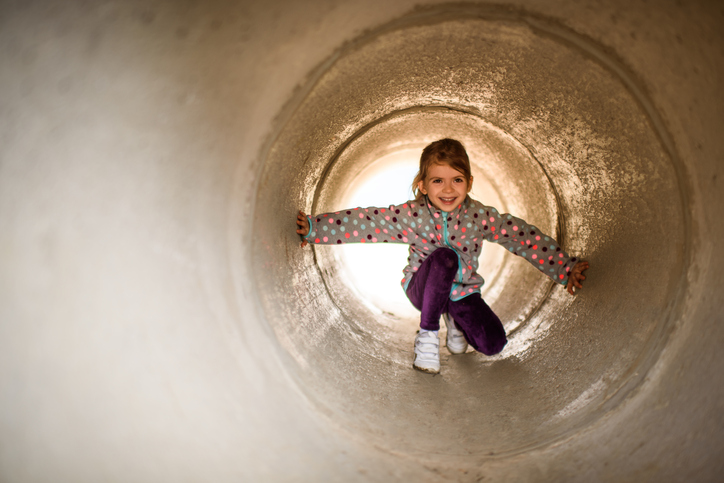 Little girl playing in the park and moving through the concrete tunnel.