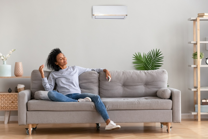African young relaxed woman sitting on couch breathing fresh air