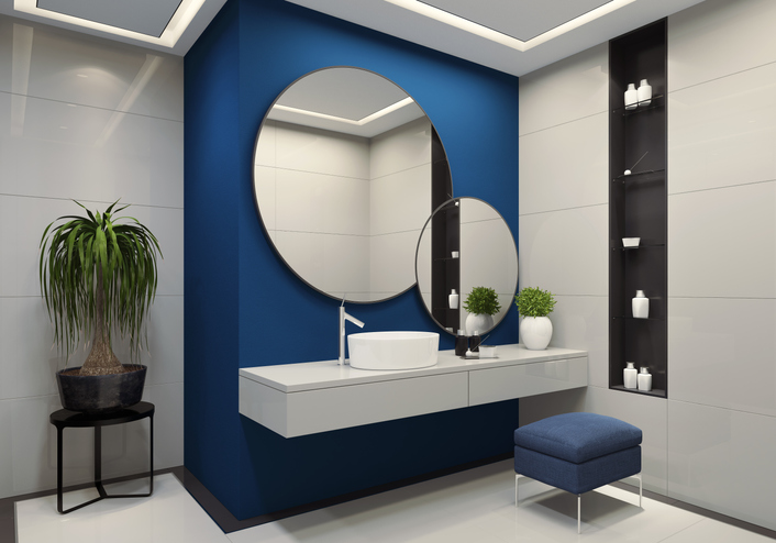 contemporary minimalist blue and white bathroom two round mirrors with black frames are on the royal blue wall. round ceramic washbasin and stainless steel basin tap is on top of the white vanity unit with two drawers. blue vanity stool is under vanity unit. walk-in shower with large white tiles and staineless steel shower panel with glass door. black wall shelves with small white cosmetic bottles. ceiling with strip cove lighting with embedded spotlights.