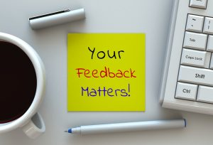 Your Feedback Matters, message on note paper, computer and coffee on table